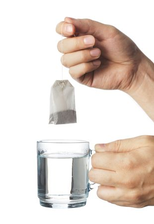 warm water: Hand zetten een theezakje in een transparant glas kopje heet water