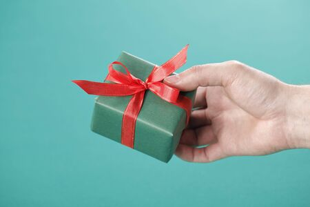Hand holding a small green gift with red ribbon. Stock Photo - 6551612