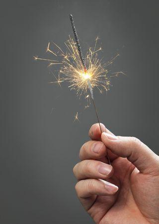 Mano sosteniendo un fuego artificial de surtidores  Foto de archivo - 6551631