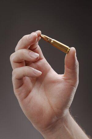 Hand holding an assault rifle cartridge Stock Photo - 6722712