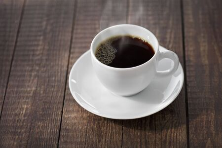 A hot cup of steaming black coffee photo