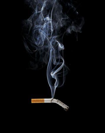 cigarrillos: Un cigarrillo de fumar sobre fondo negro Foto de archivo