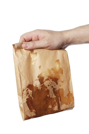 Man holding a brown paper bag with very greasy contents photo