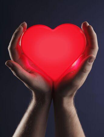 corazon en la mano: Hombre sosteniendo un coraz�n brillante color rojo en sus manos.