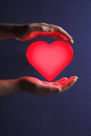 glows: Man holding a glowing red heart in his hands Stock Photo