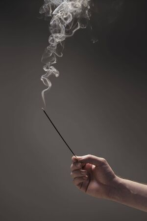 Hand of a man holding a burning incense stick. photo