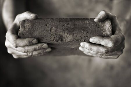 Sepia toned photo of DIrty hands holding an old brick Stock Photo - 6914172