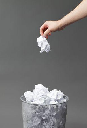 Hand mit einem zerknittertes Papier und ein überflüssiges Papier-Korb