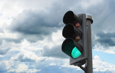 Traffic light with green light lit against sky photo