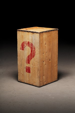 marked boxes: Old wooden crate with a photoshopped question mark on dirty concrete floor.