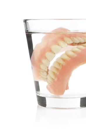 dentadura postiza: Dentaduras postizas antiguos en un vaso de agua