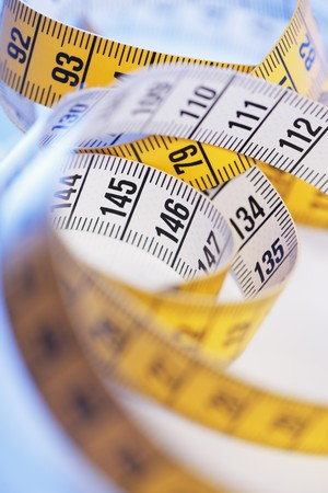 millimetres: A Yellow and white metric tape measure in closeup.