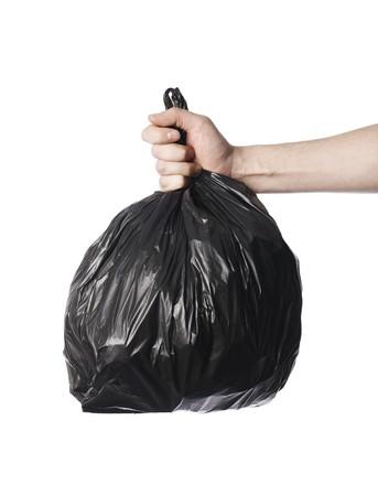 Man holding a full black plastic trash bag in his hand.