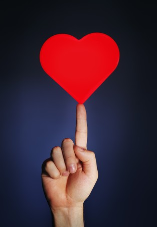 fingertip: Man holding a glowing red heart on his fingertip