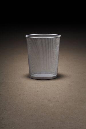 wastepaper basket: Empty wastepaper basket on dirty concrete floor