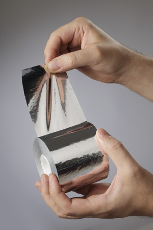 foil roll: Man holding a roll of adhesive aluminum foil tape in his hands.