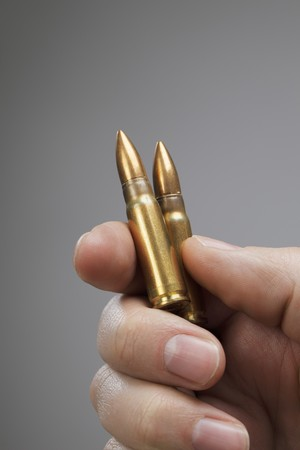 Man holding two rifle cartridges in his hand Stock Photo - 7917276