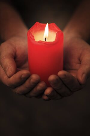 Man holding a red candle in his hands. Very short depth-of-field. Stock Photo - 7917297