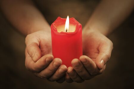 Man holding a red candle in his hands. Very short depth-of-field. Stock Photo - 7917277