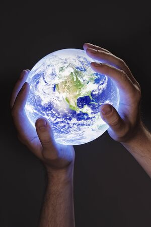 Man holding a glowing earth globe in his hands. Earth image provided by Nasa. photo