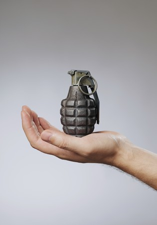 grenade: Man holding a hand grenade in his hand Stock Photo