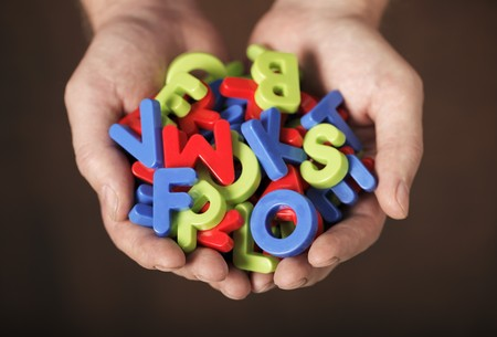 Man holding colorful plastic letters in his hands. Very short depth-of-field. Stock Photo - 7917288