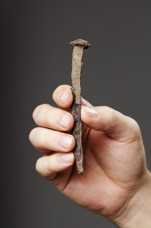 Man holding an old rusty nail in his hand Stock Photo - 7917295