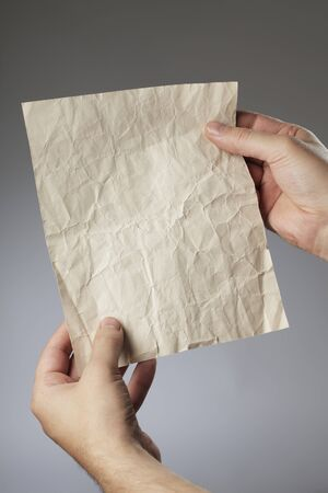 Man holding an old crumpled paper in his hands. Stock Photo - 7917320