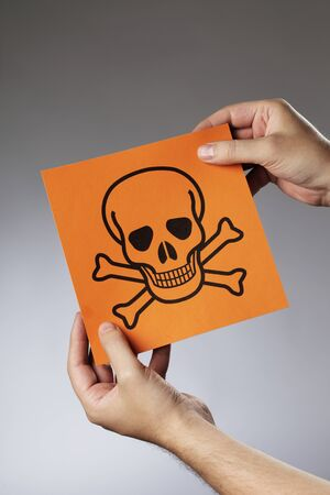 Man holding the symbol for poison in his hands. Stock Photo - 7917319