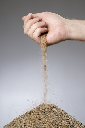 trickle down: Man adding sand in a heap with his hand