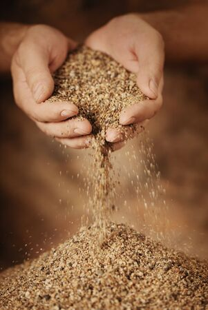 trickling: Man adding coarse sand to a heap with his hands. Very shallow depth-of-field and motion blur.