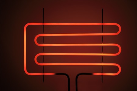 Heating element of a small electrig barbeque grill glowing.