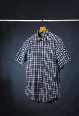 short sleeved: A short sleeved mens plaid casual summer shirt hanging on a hanger. Stock Photo