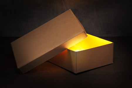 glowing light: An Old brown cardboard box with glowing contents. Stock Photo