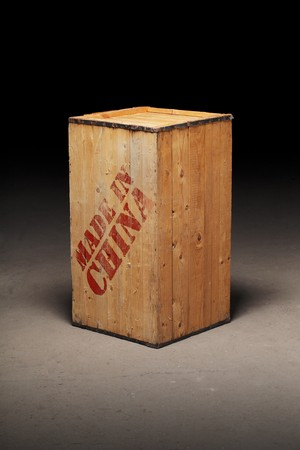 An old wooden crate with text Made in China on dirty concrete floor photo