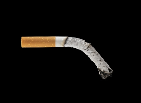 burned out: A burned out filter cigarette on black background