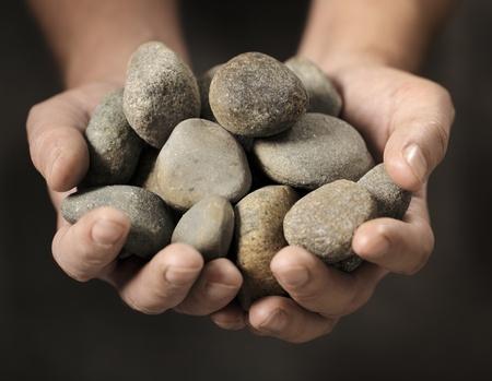 rock hand: Uomo che tiene diverse piccole rocce nelle sue mani Archivio Fotografico