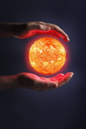 luminous: A Glowing sun between hands. Sun images provided by NASA. Stock Photo