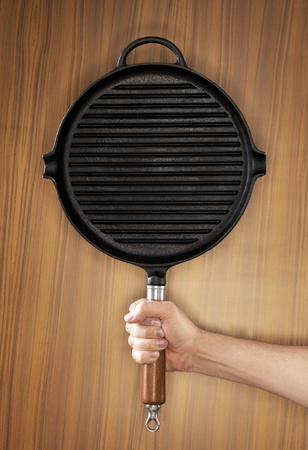 Man holding a cast iron frying pan of grill pan type. Stock Photo