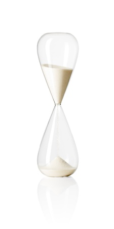 trickling: Hourglass isolated on white reflective background.