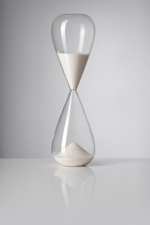trickling: A Hourglass on reflective background.