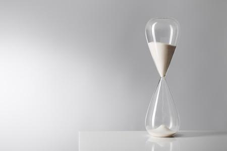 Studio photo of a hourglass on reflective table. photo
