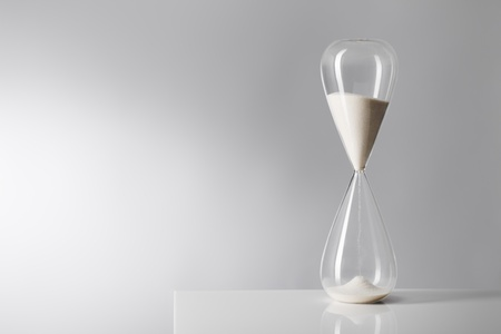sand timer: Studio photo of a hourglass on reflective table. Stock Photo