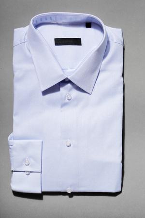 A light blue new mens dress shirt on grey background.