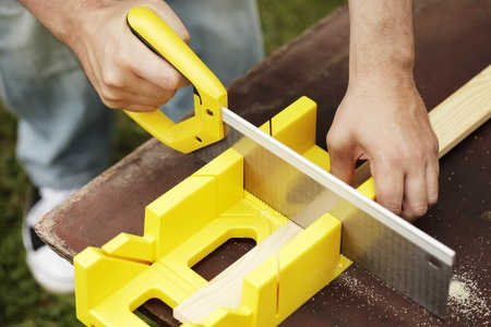 miter: Man cutting a slat of wood using a saw and miter box outdoors. Stock Photo