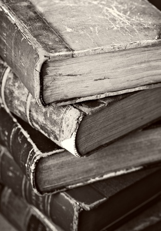 tattered: Sepia toned image of a stack of old worn books.