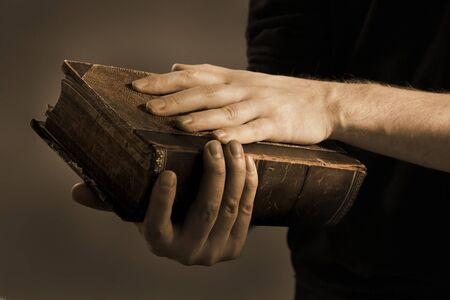 bible book: Toned image of a Man holding an old book in his hands.
