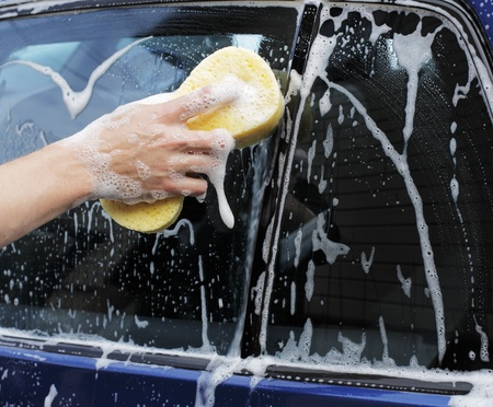 Man washing a car with a yellow sponge. photo