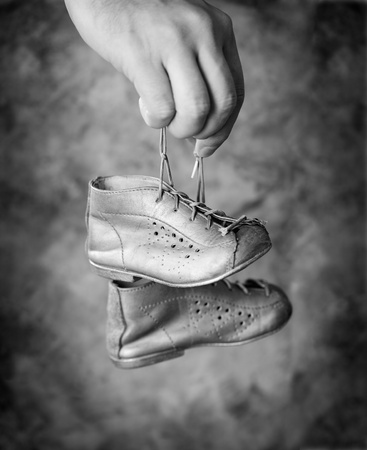Black and white image of Man holding his old baby shoes in his hand. photo