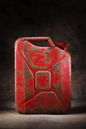 petrol can: Old red and rusty jerry can gasoline container.
